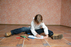 Child sitting on the floor and drawing Royalty Free Stock Photos