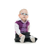 The child sitting on the floor with glasses and looks at computer. The child sitting on the floor with glasses Stock Photo