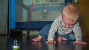 Child sitting on the floor with pacifier in front. Slow motion high quality footage of a little baby boy starting to crawl towards the pacifier who is lying in stock footage