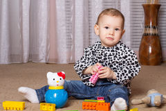Child sitting on the floor playing. Little girl playing in a room with toys Royalty Free Stock Photo