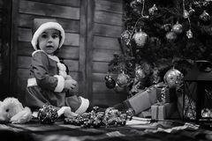 A child waiting for Santa Claus. A child sitting in front of a Christmas tree waiting for Santa Claus Stock Photography
