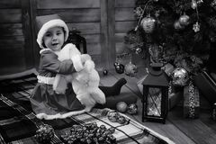 A child waiting for Santa Claus. A child sitting in front of a Christmas tree waiting for Santa Claus Royalty Free Stock Photography
