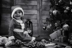 A child waiting for Santa Claus. A child sitting in front of a Christmas tree waiting for Santa Claus Stock Image