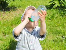 The child, sitting on the grass and drinks water from a bottle o. N a hot day. Little boy quenches thirst Royalty Free Stock Photo