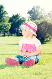 Child sitting on the grass Stock Images