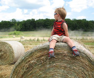 Child sitting on Hay Bale. Staring at Dirt Road on a sunny day Royalty Free Stock Images