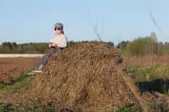 Child sitting on a haystack Royalty Free Stock Image