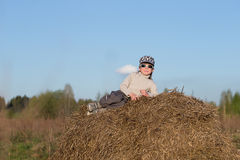 Child sitting on a haystack Royalty Free Stock Photos