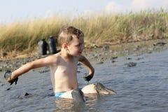 Child sitting in the healing mud Stock Photo