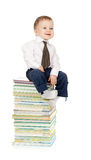 Child sitting on the heap of books. Toddler dressed in suit and sitting on the heap of books Royalty Free Stock Photography