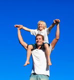 Child sitting on his father's shoulders. Happy child sitting on his father's shoulders Royalty Free Stock Photos