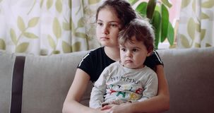 A child sitting in his sister`s arms and look focused. 4k stock footage
