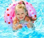Child sitting on inflatable ring in swimming pool. Little girl sitting on inflatable ring in swimming pool royalty free stock photos