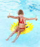 Child sitting on inflatable ring thumb up. Stock Image