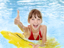 Child sitting on inflatable ring thumb up. Stock Images