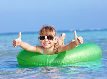 Child sitting on inflatable ring thumb up. Stock Photos