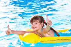 Child sitting on inflatable ring thumb up. Royalty Free Stock Photos