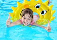 Child sitting on inflatable ring thumb up. Royalty Free Stock Images
