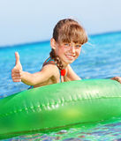 Child sitting on inflatable ring thumb up. Royalty Free Stock Photo