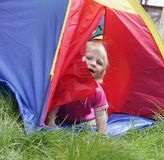 Child sitting inside colorful tent Stock Photos