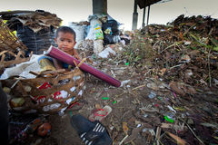 Child is sitting in a landfill Stock Photos