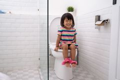 Child sitting and learning how to use the toilet. Adorable young child sitting and learning how to use the toilet stock images
