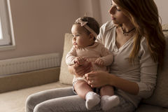 Child sitting in mother`s lap. Mother sitting on a living room couch with her baby girl in her lap, looking away from the camera, pensive Stock Photos