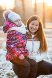 Child sitting with mother on a walk in park, the sun's rays of sunset Stock Image