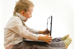 Child sitting with notebook on his legs Stock Images