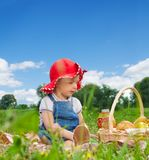 Child sitting with picnic basket Stock Image