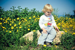 Child sitting on a rock Stock Photo