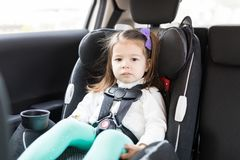 Child Sitting On Safety Seat In Car. Adorable female child secured with seat belts in car stock images