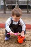 Child sitting in sandbox making mud pie Stock Image
