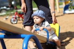 Child sitting on seesaw Stock Image
