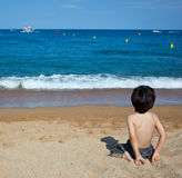 Child sitting on the shore Stock Photos