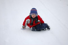 Child  is sitting on the snow Stock Images