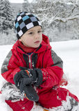 Child sitting in snow Stock Image