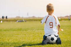 Child sitting on soccer ball on the football pitch. Kid in sports jersey uniform watching soccer training stock image