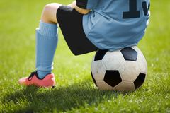 Child Sitting on Soccer Ball. Young Boy with Soccer Ball on the Pitch Stock Photos
