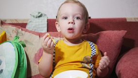 A child is sitting on the sofa at home and watching TV. Eat corn sticks and smile.  stock video footage