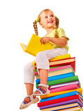 Child sitting on stack of books. Stock Photo