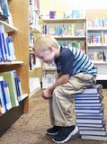 Child sitting on a stack of books. Young child sitting on a stack of books searching for the perfect book at the library royalty free stock images