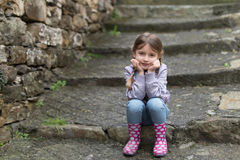 Child sitting on stairs outdoors Stock Photos