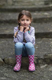 Child sitting on stairs outdoors Stock Image
