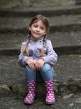 Child sitting on stairs outdoors Royalty Free Stock Images
