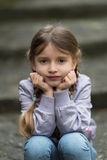 Child sitting on stairs outdoors Royalty Free Stock Photo