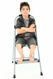Child Sitting on Step Ladder Arms Crossed. Attractive 8 year old boy child sitting with arms crossed on step ladder over white background Royalty Free Stock Photos