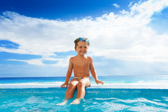 Child sitting on stoned boarder with legs in water Royalty Free Stock Images
