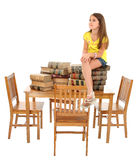 Child Sitting on Table of Books Stock Photo