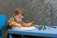 Child sitting at a table drawing Stock Photography